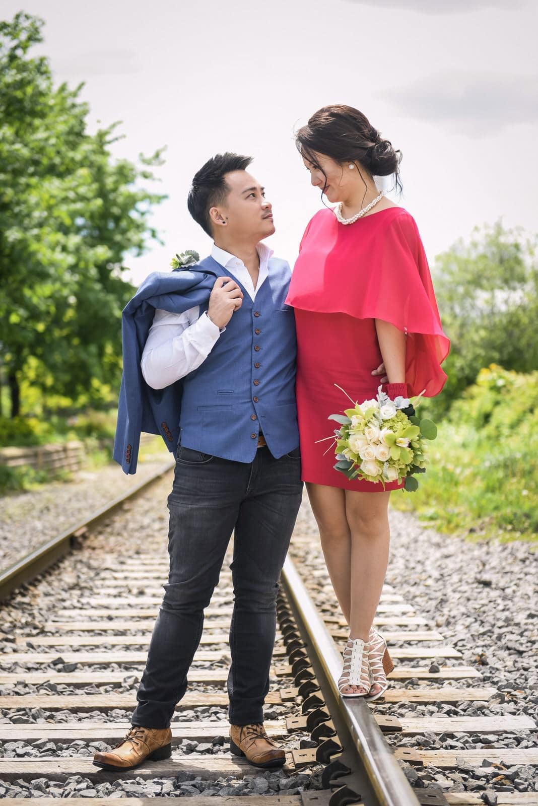 michelle evan couple engagement session casual style stylish love montreal alain simon fleurs asian prewedding photoshoot suit blue red dress matching pearl outfit laugh railroad